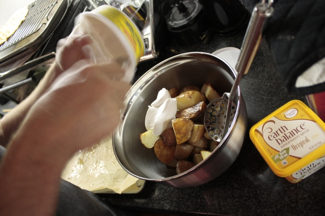 vegan cream cheese being added to roasted potatoes